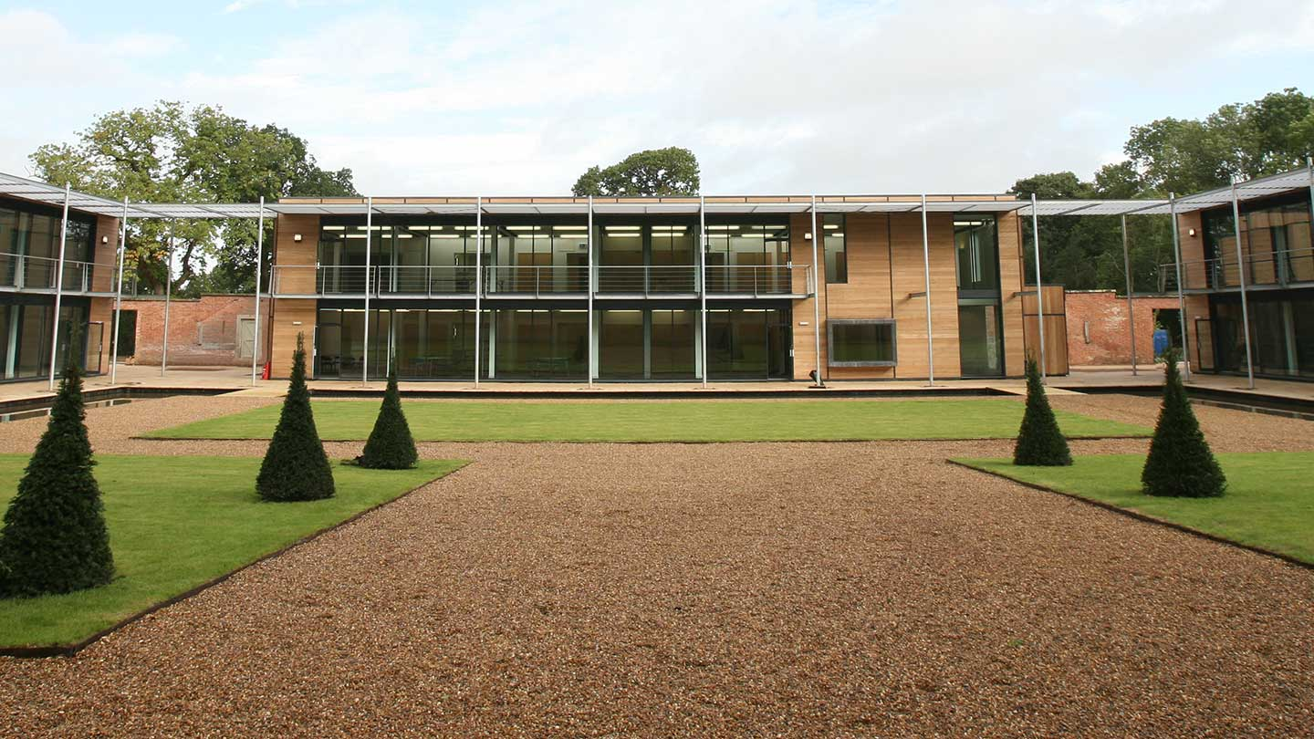 glass-fronted office building with lawns and gravel