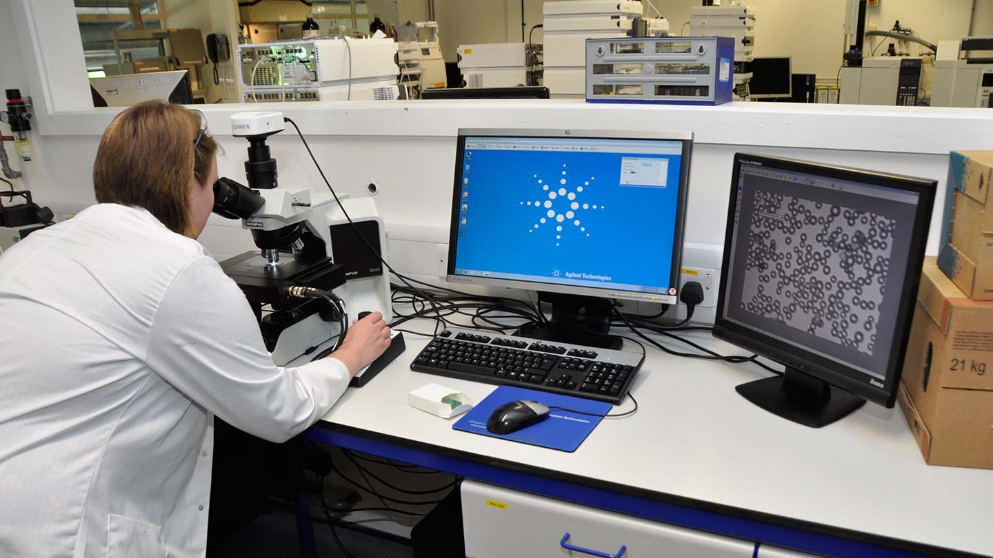 Lab technician using microscope with two computer monitors