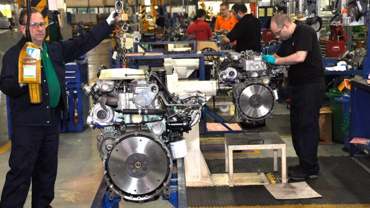 Engineers working on machinery in the warehouse