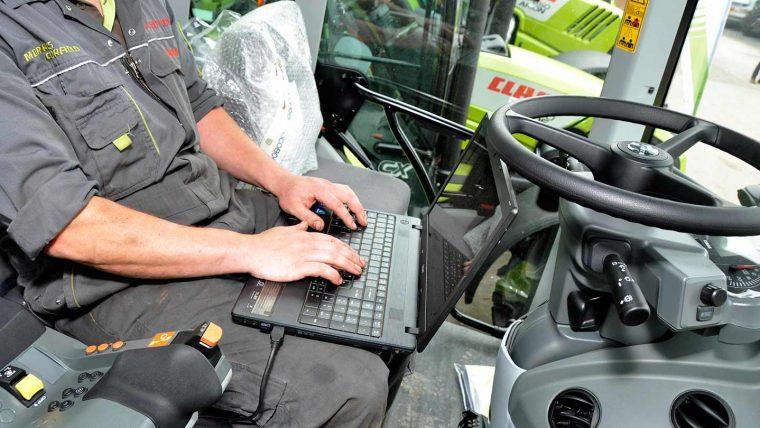 Workman in overalls using laptop in tractor