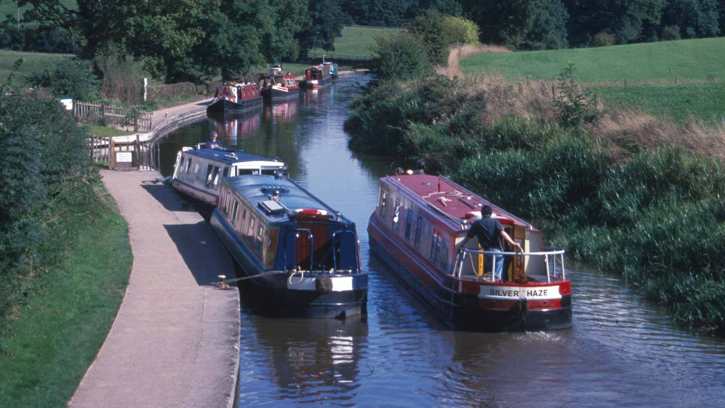 Barge moving down canal, past moored barges