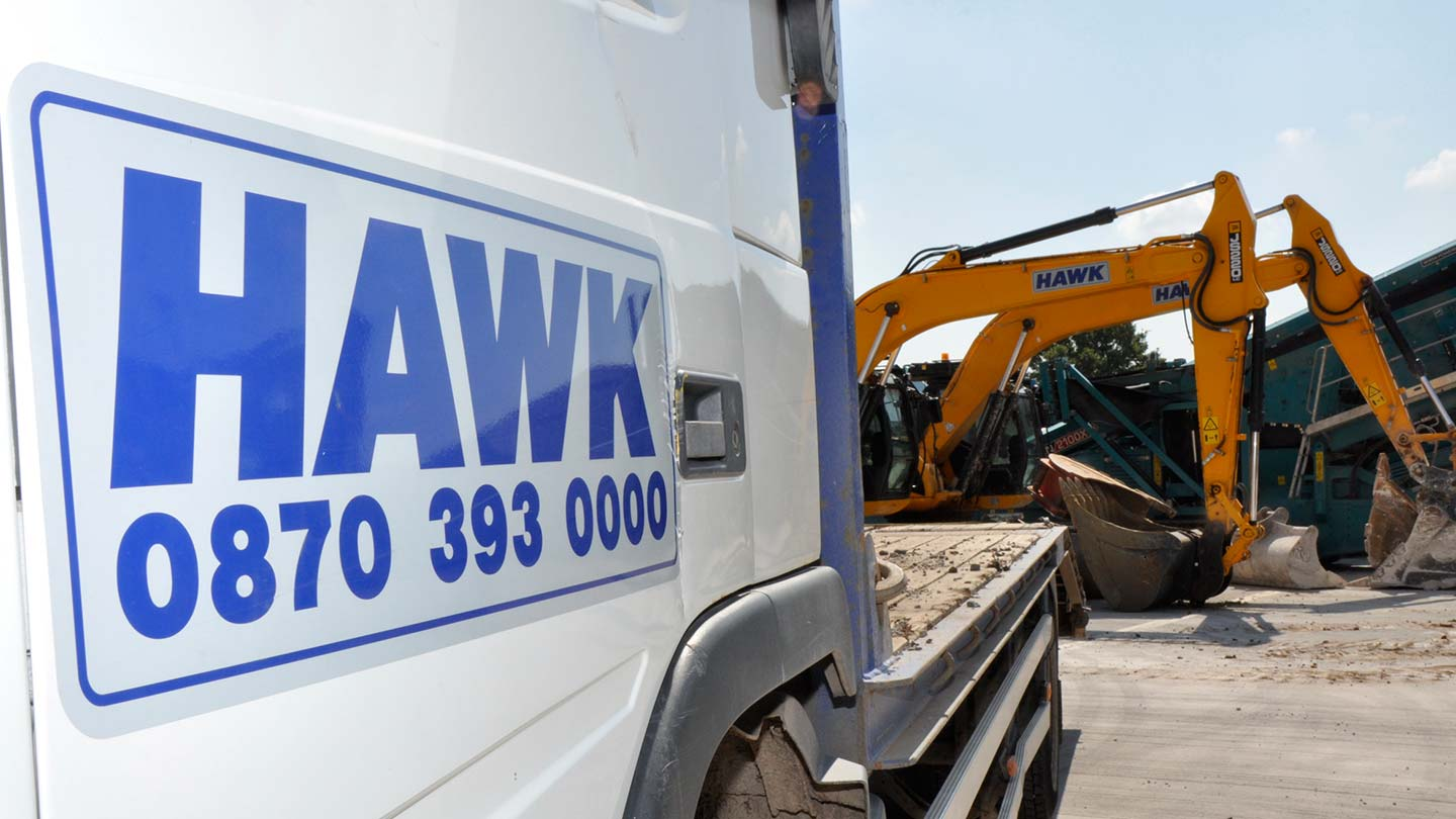 Side on view of Hawk logo on side of lorry, with heavy machinery in background