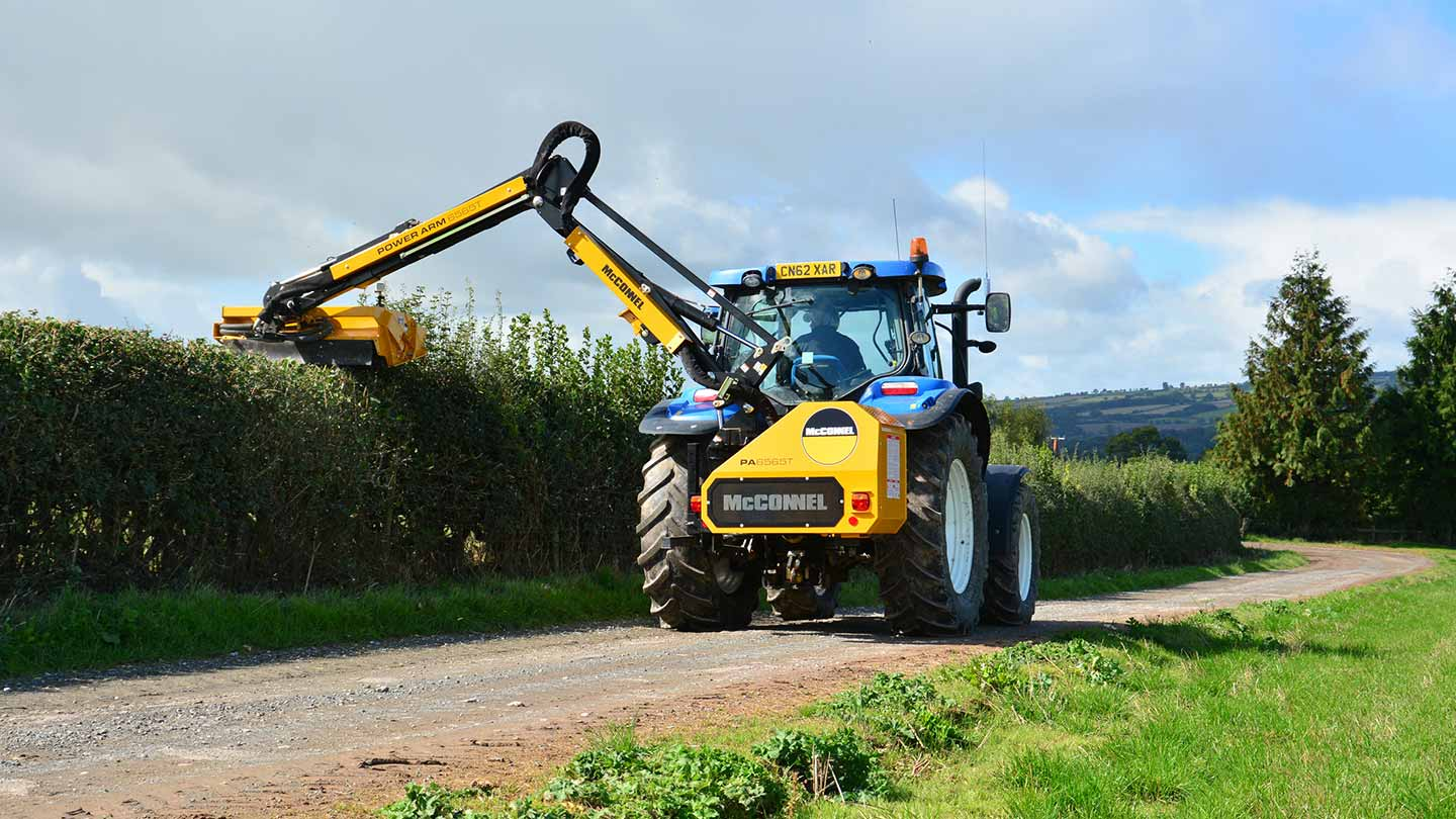Hedge cutter traveling down country lane