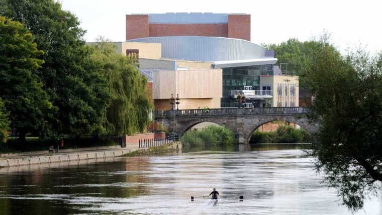 Man rowing along the River Severn with Theatre Severn in background