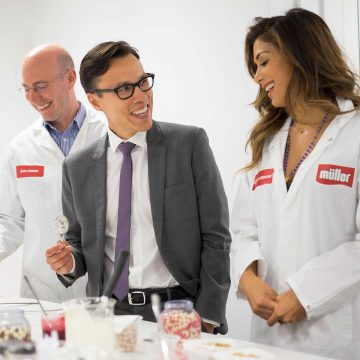 Three smiling colleagues, one in suit, 2 in white jackets tasting ingredients