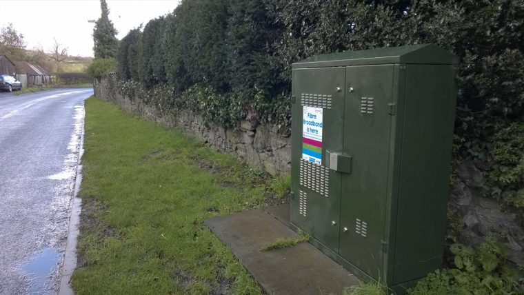 Green fibre broadband cabinet on grass by side of the road