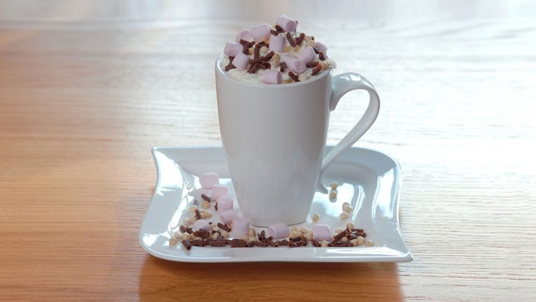 Hot chocolate in a white mug on a saucer covered in marshamallows and chocolate sprinkles