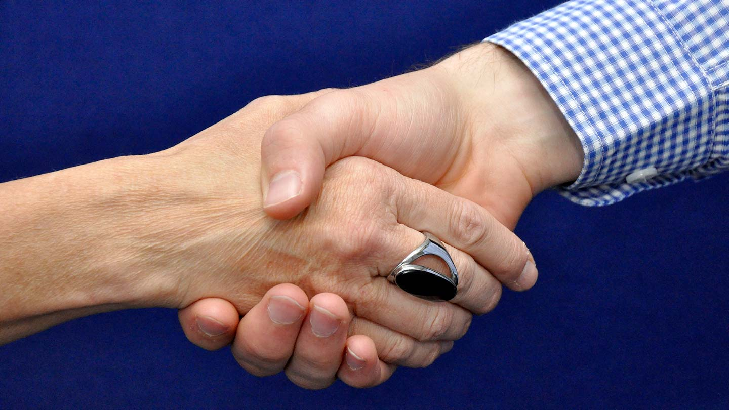 two people shaking hands wearing check shirt and black ring