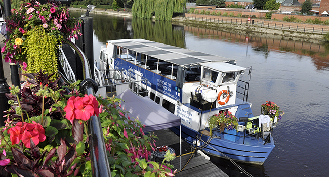 passenger boat on river severn moored to bank with pink flowers in foreground